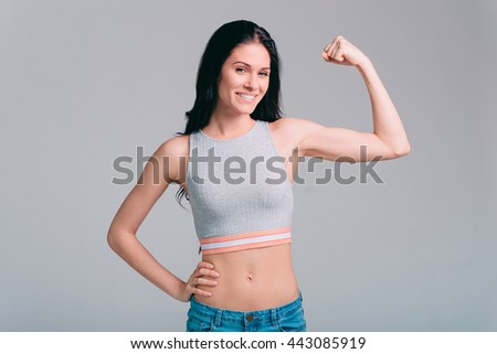 Confident in her body. Attractive young sporty woman showing her bicep and smiling while standing against grey background - stock photo