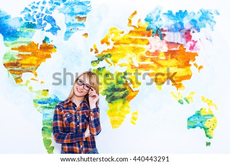 Confident in her future. Cheerful young women adjust her glasses and smiling while standing against map of the world. - stock photo