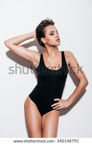 Confident in her perfection. Beautiful young short hair woman in black swimsuit keeping eyes closed while posing against white background - stock photo