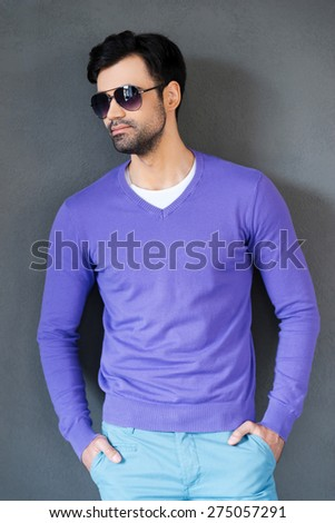 Confident in himself. Handsome young man in sunglasses holding hands in pockets and looking away while standing against grey background - stock photo