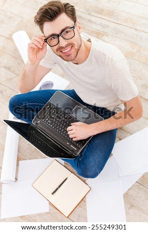 Confident in his new project. Top view of young man working on laptop and looking at camera with smile while sitting on the floor at home - stock photo