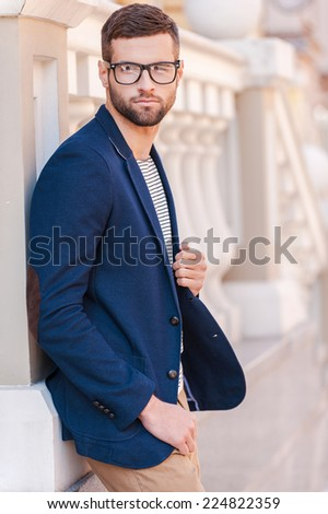Confident in his perfect style. Handsome young man in eyeglasses and smart jacket looking away while standing outdoors - stock photo