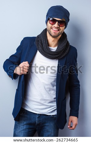 Confident in his perfect style. Handsome young stylish man in sunglasses and hat adjusting his jacket and looking at camera while standing against grey background - stock photo