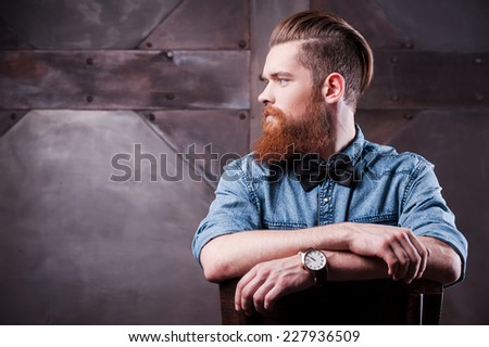 Confident in his perfect style. Profile of a handsome young bearded man looking away and sitting on chair  - stock photo