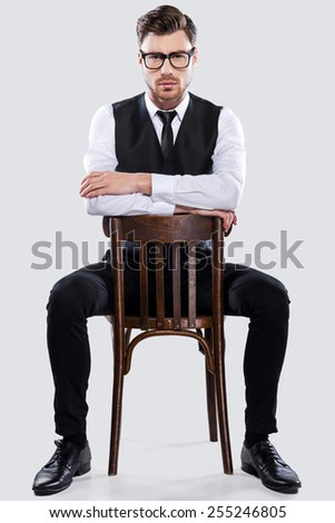 Confident in his style. Handsome young man in formalwear sitting at the chair and looking at camera while standing against grey background - stock photo