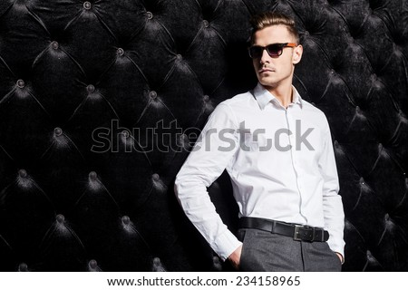 Confident in his style. Handsome young man in white shirt holding hands in pockets and looking away while standing against black background  - stock photo
