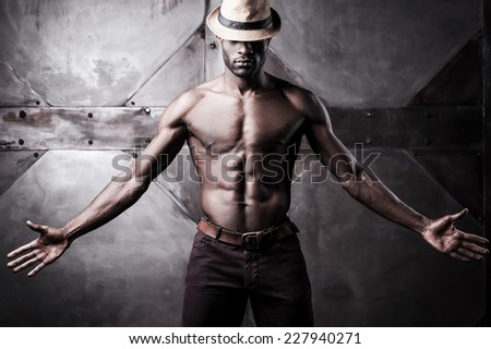 Confident in his style. Handsome young shirtless African man in hat stretching out hands while standing against metal background - stock photo