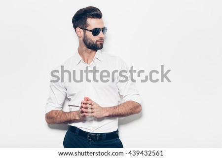 Confident in his style. Stylish young man in white shirt looking away and keeping hands clasped while standing against white background  - stock photo