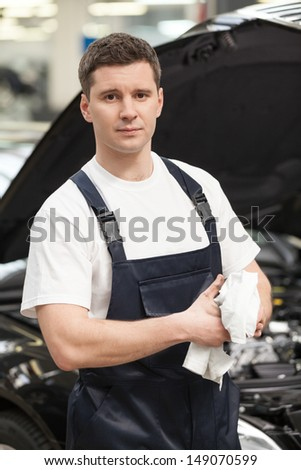 Confident in his work. Close-up of mechanic wiping his hands with handkerchief while standing in front of the car - stock photo
