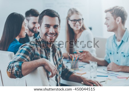 Confident in my team. Group of cheerful business people in smart casual wear sitting together at the table and discussing something while handsome man looking at camera and smiling