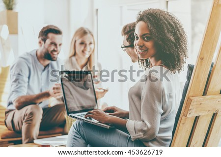 Confident in my team. Smiling young African woman working on laptop while her colleagues discussing something in the background - stock photo