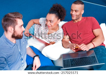 Confident in their team. Group of cheerful creative professionals in smart casual discussing something with laptop in teamwork while sitting in creative space  - stock photo