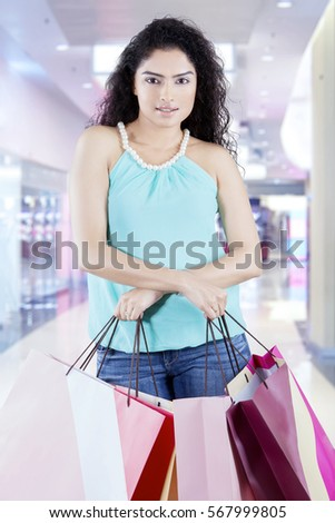 Confident Indian woman looking at the camera while holding much shopping bags at the mall