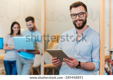 Confident IT expert. Cheerful young man holding digital tablet and smiling while his colleagues working in the background - stock photo