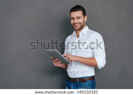 Confident IT professional. Handsome young man holding digital tablet and smiling while standing against grey background - stock photo