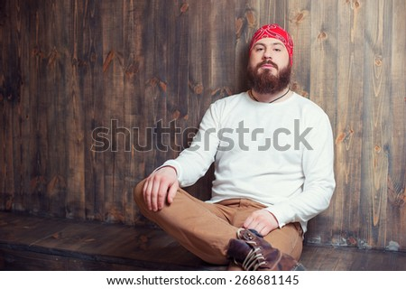 Confident lambersexual. Portrait of young bearded man sitting against wooden wall. - stock photo