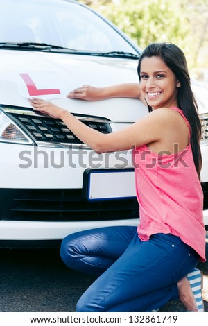 Confident learner driver girl proud of passing her test with car - stock photo