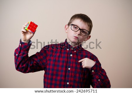 Confident little boy nerd ,holding a puzzle cube  pointing with finger to his self and felling proud.Concept happy,nerd. - stock photo
