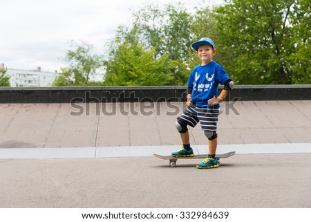 Confident little boy with a big friendly smile standing with his skateboard on the tarmac at the skate park on a hot summer day, with copyspace - stock photo