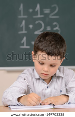 Confident little schoolboy. Confident little boy writing something in his note pad while sitting in front of the blackboard - stock photo