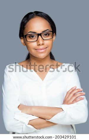 Confident look. Attractive young African woman adjusting her eyeglasses and looking at camera while standing against grey background - stock photo