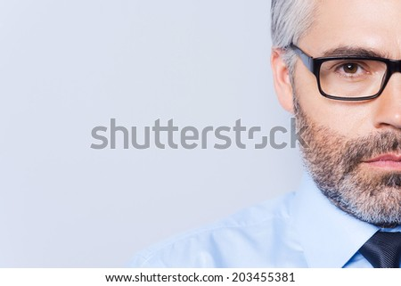 Confident look. Half full portrait of confident mature man in shirt and tie looking at camera and while standing against grey background - stock photo