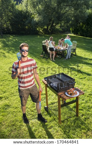 Confident looking man standing with kitchen utencils in a park with a few friends in the background in the late summer afternoon - stock photo