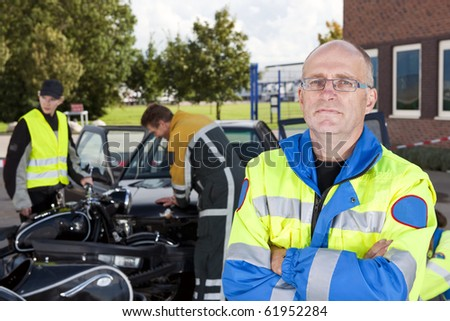 Confident looking paramedic posing for the camera in front of a car crash