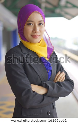 Confident Looking Young Muslim Woman at the Train Station - stock photo