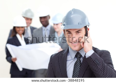 Confident male architect with his team in the background smiling at the camera