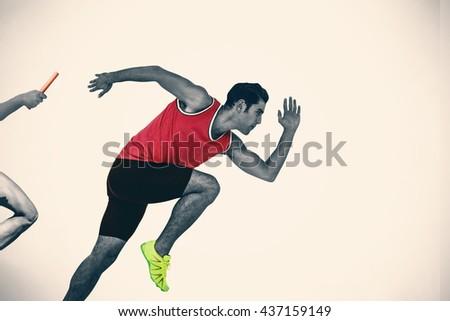 Confident male athlete running from starting blocks against white background - stock photo