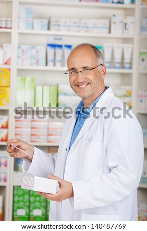 Confident male pharmacist holding medicine and prescription paper in pharmacy - stock photo