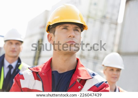Confident male worker with colleague in background at shipping yard - stock photo