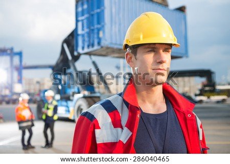 Confident male worker with colleagues in background at shipping yard - stock photo