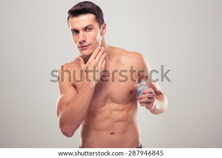 Confident man applying facial lotion over gray background - stock photo