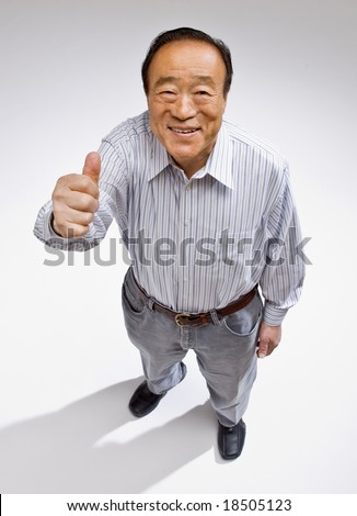 Confident man giving thumbs up gesture enthusiastically - stock photo