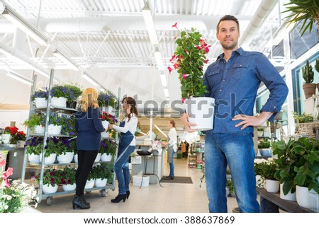 Confident Man Holding Flower Plant In Shop - stock photo