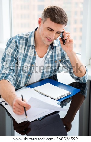 Confident man in checkered shirt sitting at the table with bills and talking on cell phone  - stock photo