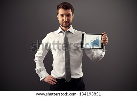 confident man in formal wear showing growth chart over dark background - stock photo