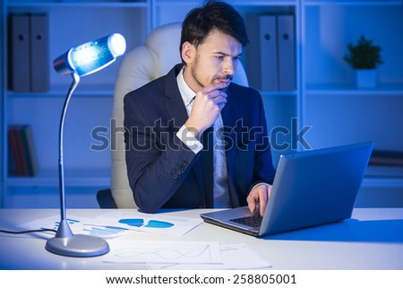 Confident man is working on laptop in office. - stock photo