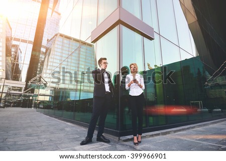 Confident man lawyer having mobile phone conversation, while his woman colleague is searching information on web page via cellphone. Two office workers are using cell telephones during break at job - stock photo