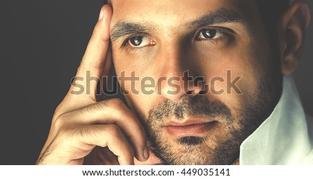 Confident man looking to the side. Businessman thinking with a finger on the forehead - stock photo