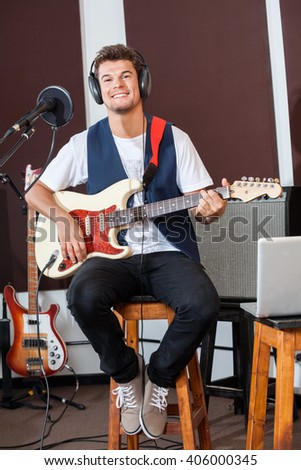 Confident Man Playing Guitar While Sitting On Stool - stock photo