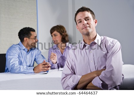 Confident man (30s) in business meeting, colleagues talking in background