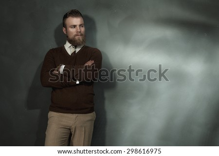 Confident man standing with folded arms leaning against a grey wall with a side lit beam of light staring thoughtfully to the side