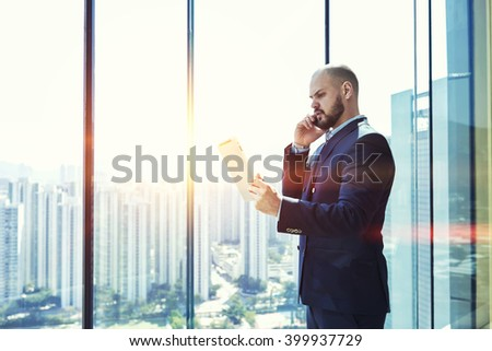 Confident man successful entrepreneur dressed in suit is reading the monthly report on portable digital tablet and talking via cell telephone with manager his company during business trip in New York - stock photo