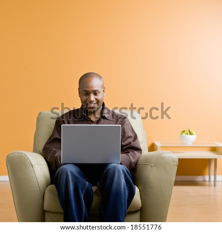 Confident man typing on laptop in livingroom - stock photo