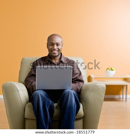 Confident man typing on laptop in livingroom - stock photo