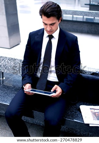 Confident man using digital tablet computer while sitting on the bench in hall of railway station,successful businessman on way to work reading news on his touch pad, executive receiving news on email - stock photo