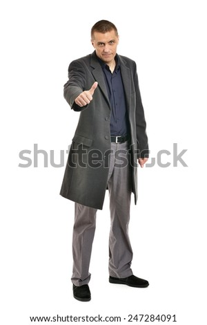 Confident man with thumbs up in coat on a white background - stock photo